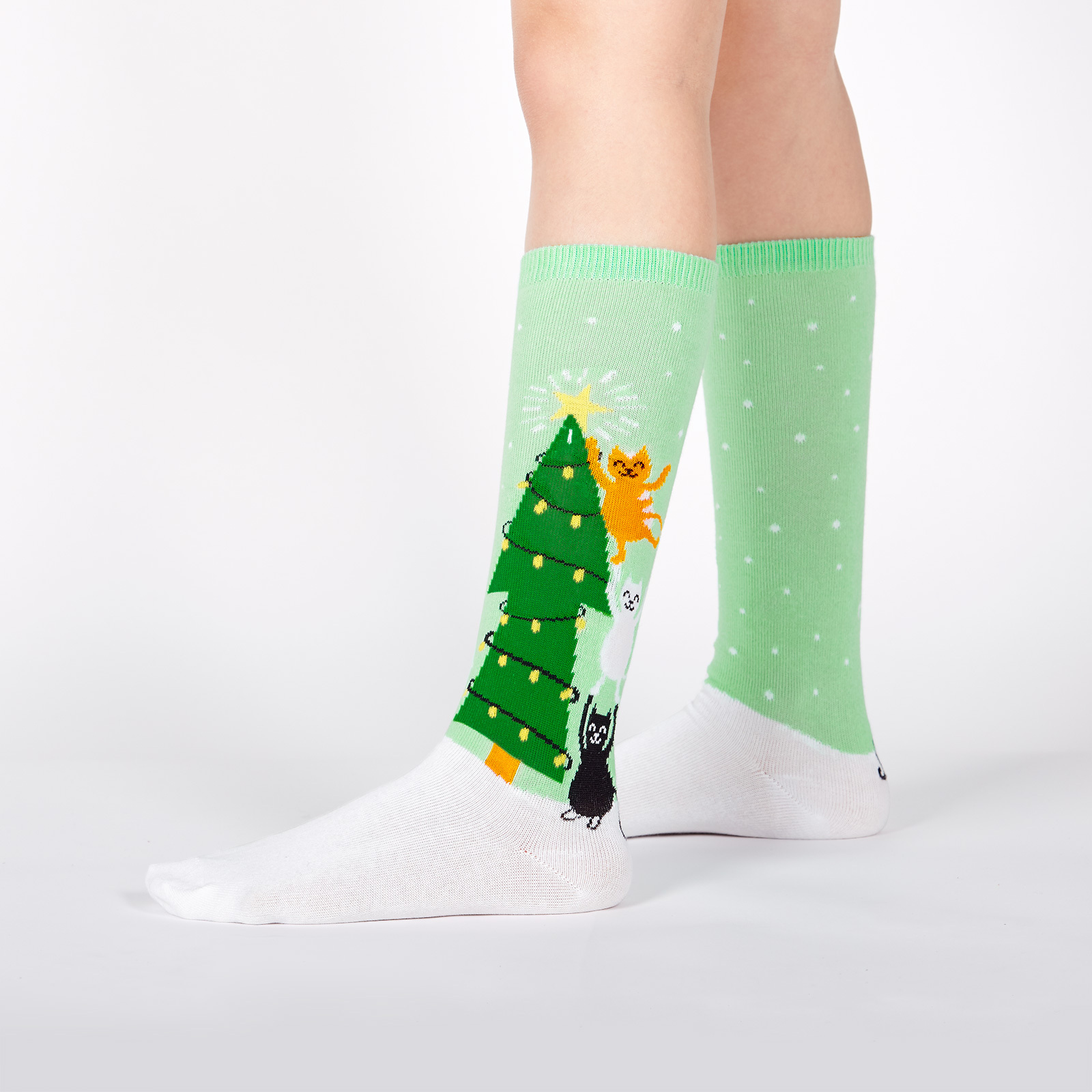 model wearing Naughty or Nice - Winter Cats Decorating Christmas Tree Snow Knee High Socks Green - Youth